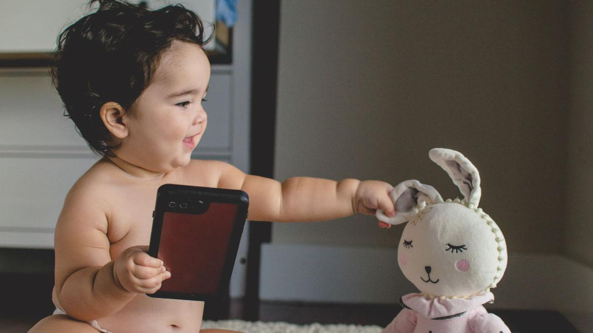 Hispanic baby holding a phone